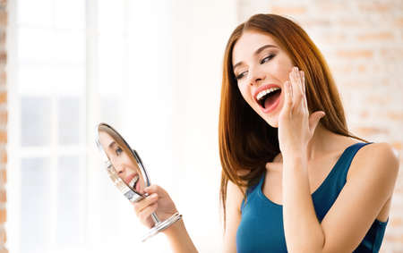 Image of happy excited attractive woman with mirror at home. Beautiful girl in casual blue dress - make up and beauty treatment concept.