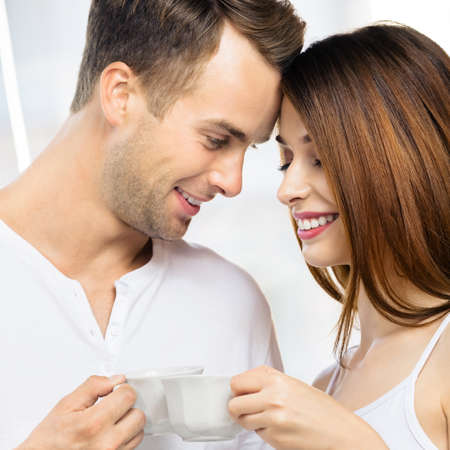 Image of smiling happy amazed couple with cups of some drinks at home. Portrait of standing close and looking at each other models in love family concept. Man and woman posing together. Square. Standard-Bild