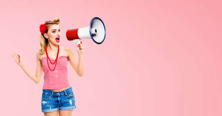 Image of blond haired woman holding megaphone, shout something. Girl in red pin up style, isolated over rose pink colour back. Female model in retro vintage studio concept.