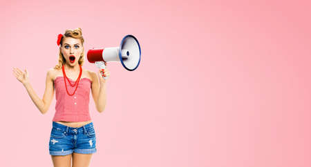 Image of beauty blond haired woman holding megaphone, shout something. Girl in red pin up style clothing, isolated over rose pink colour back. Female model in retro vintage concept. Standard-Bild