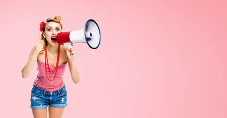 Blond haired woman holding megaphone, shout something. Girl in red pin up style clothing, over rose pink colour. Female model in retro vintage studio concept.