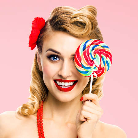 Square image - half face portrait of excited blond woman with lollipop covering one eye. Pin up girl with happy smile. Retro style. Rose pink colour back. Ophthalmology concept.