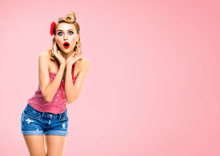 Unbelievable news! Excited surprised, very happy blondy hair woman. Pin up syle girl with opened mouth and raised hands. Retro and vintage concept. Rose pink color background. Standard-Bild