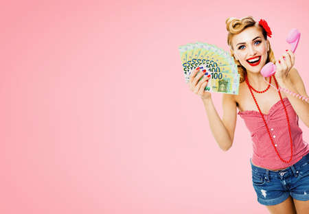 Happy smiling woman with money cash, talking on phone, dressed in pin up style, over rose pink color background. Caucasian blond girl in retro fashion and vintage concept. Standard-Bild