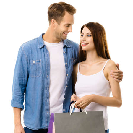Image of young smiling couple with shopping bags, standing close and looking to each other. Love, holiday sales, shop, retail, consumer concept, isolated on white background.