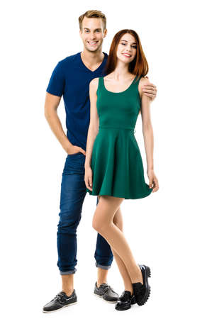 Image of smiling young couple. Full body length portrait of standing close and looking at camera models at happy in love studio concept, isolated on white background. Man and woman posing.