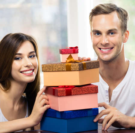 Square image of happy excited smiling couple with gifts boxes, at home. Shopping, holiday sales, love, relationship concept - young man and woman, indoors.