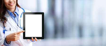 Close up of happy smiling female doctor showing tablet pc touchpad with blank copy space area for some text, over blurred modern office background. Medical help call center concept.
