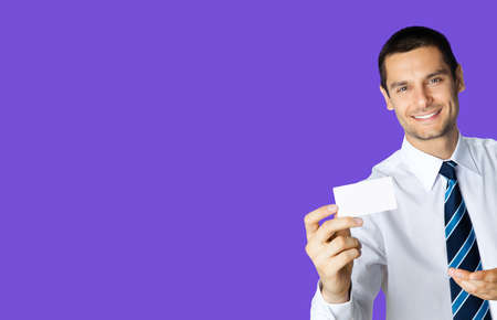 Happy smiling businessman in white shirt and tie, showing blank business or plastic credit card, copy space area for text or sign, violet purple colour background. Confident business man at studio.