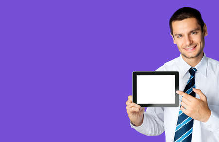 Happy smiling businessman in white shirt and tie, showing pointing tablet pc, touchpad, with copy space area for text or slogan, over violet purple colour background. Confident business man at studio.