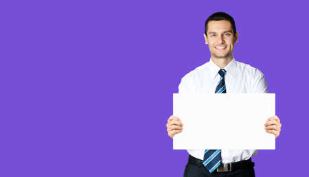 Happy smiling businessman in white shirt and tie, showing blank signboard with copy space area for text or sign, violet purple colour background. Confident business man holding paper board at studio.