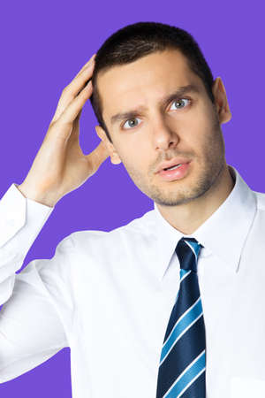 Portrait of puzzled, shocked young brunette businessman in white shirt and tie, isolated over violet purple colour background with copy space area. Confident business man at studio image.