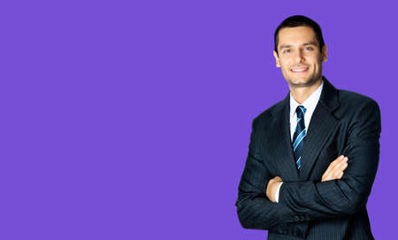 Portrait of happy smiling brunette businessman in black suit, white shirt and blue stripes tie, standing in crossed arms pose, over violet purple background with copy space. Confident business man. Standard-Bild