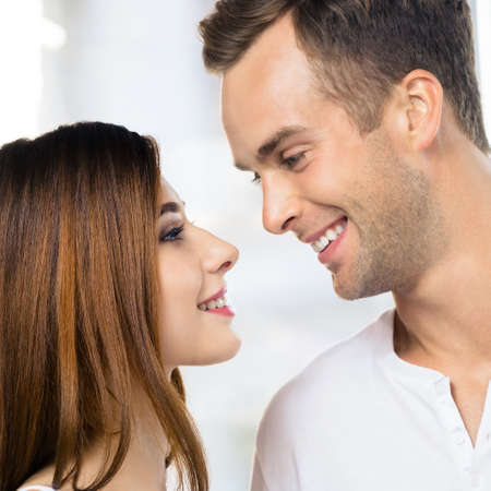 Profile side image of smiling happy amazed couple at home. Face portrait of standing close and looking at each other man and woman in love concept. Square picture.