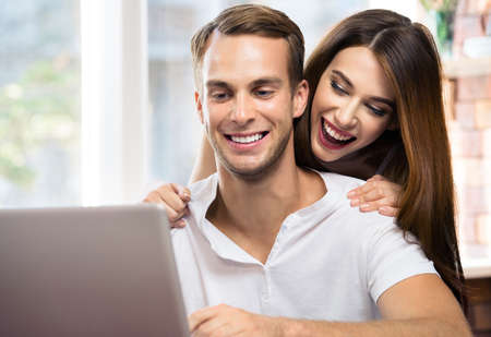 Iage of happy excited smiling couple using laptop at home. Internet, shopping, online store concept - man and woman with domestic computer. Square composition.
