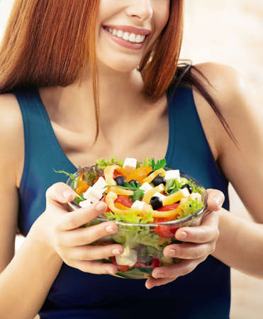 Close up of happy smiling woman with greece salad with cheese, indoor. Beautiful girl in casual green dress - dieting, weight loss, healthy vegetarian eating concept. Standard-Bild