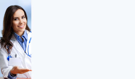 Portrait image of smiling female doctor showing blank signboard with copy space area for some text, at office. Young brunette woman in medical, clinic, healthcare concept