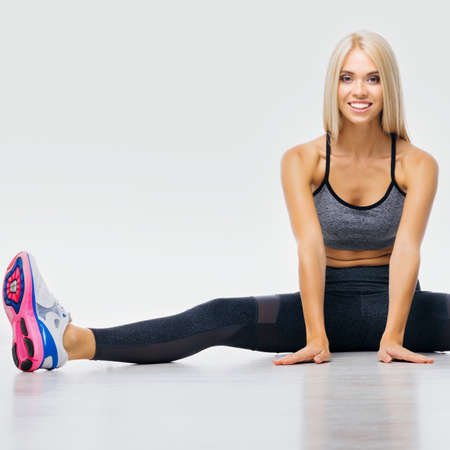 Portrait of happy smiling beautiful woman doing twine stretching exercise, sitting on floor, isolated over grey. Attractive blond girl in leggings and top - fitness studio concept.