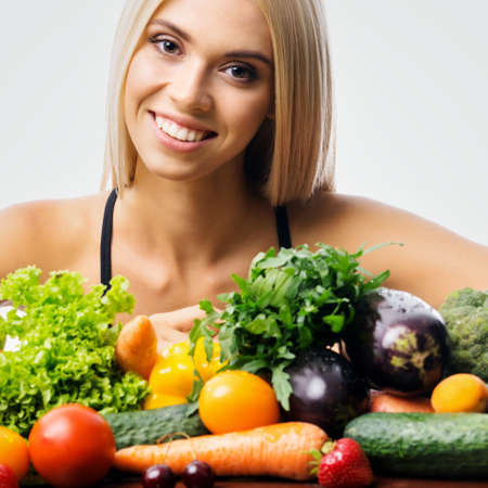 Portrait image of happy smiling young beautiful blond woman with healthy vegetarian food. Girl in dieting, loss weight and healthy eating concept. Square. Standard-Bild
