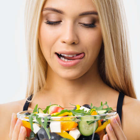 Image of blond woman with tongue lick mouth, looking at glass plate of greece salad. Blonde girl at studio. Keto diet, ketogenic weigh loss, vegetarian concept. Square composition.