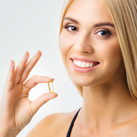 Image of smiling woman holding Omega 3 fish oil capsule. Beautiful blond girl in health care and medical studio concept. Square composition.