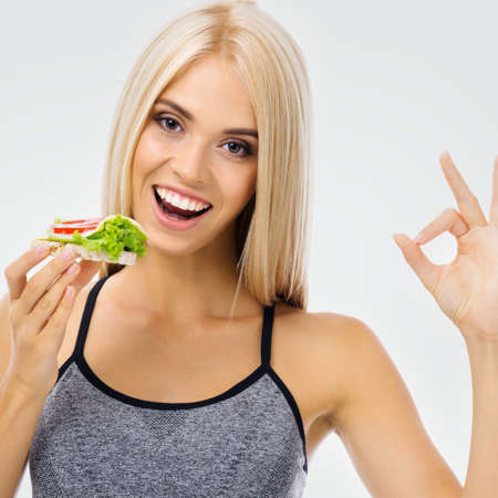 Image of happy excited woman eating vegetarian sandwich, showing ok gesture. Beautiful blond amazed smiling girl in dieting, loss weight and vegetarian concept.