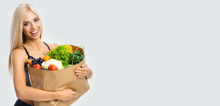 Image of smiling beautiful woman in casual cloth, holding grocery shopping bag with vegetarian raw food, isolated over grey background with copy space. Blond girl in dieting, loss weight concept.