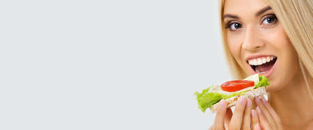 Image of happy woman eating vegetarian sandwich, over grey background with copy space. Beautiful blond smiling girl in dieting, loss weight and vegetarian concept.