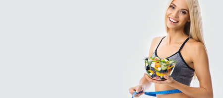 Woman in sportswear with tape measure and greece salad with vegetables and cheese, over grey background with copy space. Girl in dieting, loss weight and fitness studio concept. Wide picture.