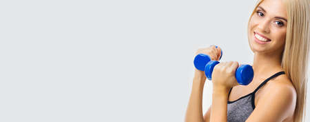 Beautiful smiling woman exercising with blue dumbbells, over grey color background. Blond girl in fitness studio concept. Wide banner composition image. Standard-Bild