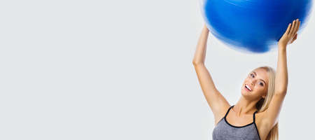 Beautiful smiling woman in sportswear holding fitness blue ball, isolated over grey color background. Blond girl in fit exercising studio concept. Wide banner composition.