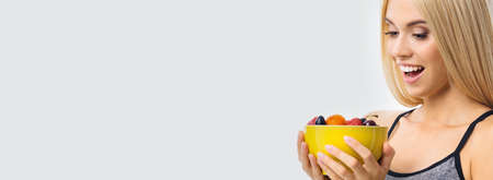 Image of happy excited woman holding yellow bowl plate of fruits, over grey background with copy space. Beautiful blond amazed smiling girl in dieting, loss weight and fitness concept.