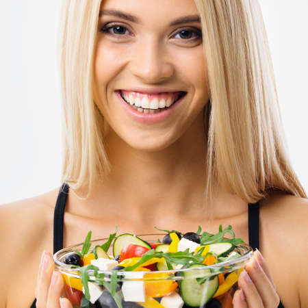 Image of happy smiling blond woman with glass plate of greece salad, over grey background. Blonde girl at studio. Keto diet, ketogenic weigh loss, vegetarian concept. Square.