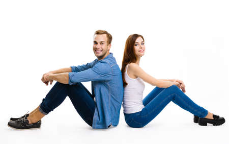 Smiling attractive young couple. Full body profile portrait of sitting back to back models in love studio concept, against white background. Man and woman posing together. Standard-Bild
