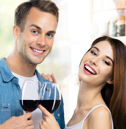 Attractive smiling young couple drinking redwine. Portrait image of caucasian models with red wine glasses in love concept. Man and woman posing together indoor. Square composition. Standard-Bild