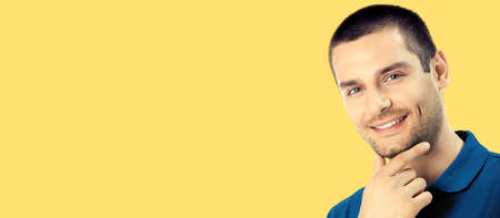 Portrait of happy smiling young man, isolated over yellow colour background. Male caucasian model in blue casual cloth at studio. Copy space area place for text. Standard-Bild