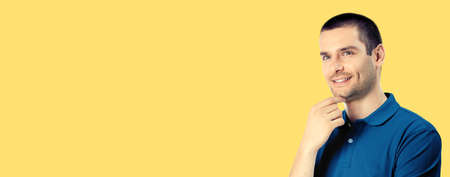 Portrait of smiling dreaming thinking man, isolated over yellow colour background. Male caucasian model at studio. Copy space empty area place for text.