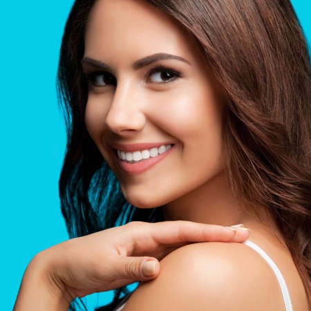 Portrait of smiling beautiful woman in white casual tank top looking at camera, over aqua blue green background. Brunette girl at studio concept.