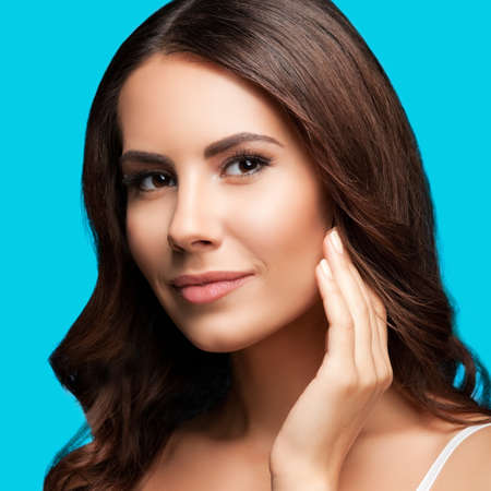 Portrait of beautiful woman in white casual tank top, over aqua blue green background. Brunette girl at studio beauty concept. Square composition image.