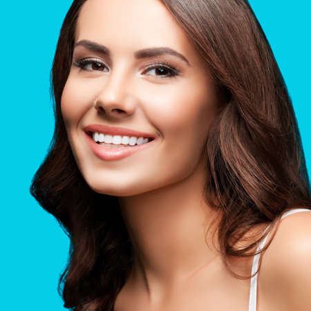 Portrait of smiling beautiful woman in white casual tank top, over aqua blue green background. Brunette girl at studio concept. Square composition.