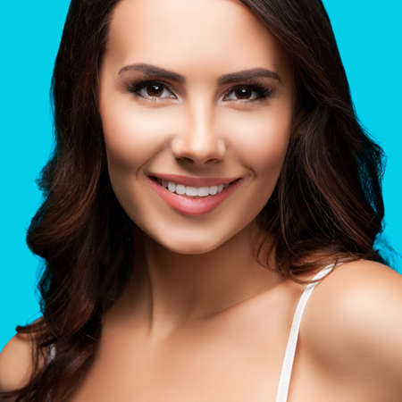 Portrait of smiling beautiful woman in white casual tank top, over aqua blue green background. Brunette girl at studio beauty concept. Square composition.
