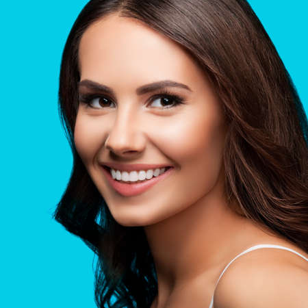 Portrait of smiling beautiful woman in white casual tank top looking at camera, over aqua blue green background. Brunette girl at studio concept. Square composition. Standard-Bild