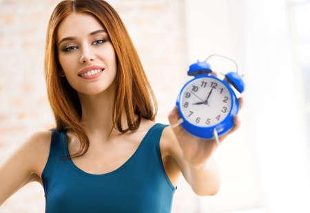 Image of attractive smiling brunette woman holding alarmclock. Beautiful girl in casual blue dress standing against window, indoors. Standard-Bild