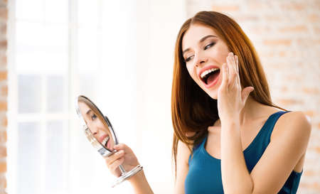 Portrait of happy excited brunette woman with mirror, indoors. Beautiful girl in casual blue dress - make up and beauty treatment concept. Standard-Bild