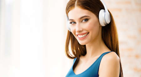 Portrait image of happy smiling attractive woman listening music in headphones at home. Beautiful girl in casual blue dress standing near window.