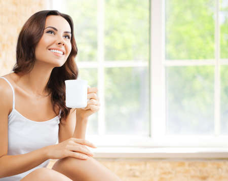 Portrait of happy smiling brunette woman in white lingerie drinking coffee or tea, looking up, at home, near window and loft style wall.