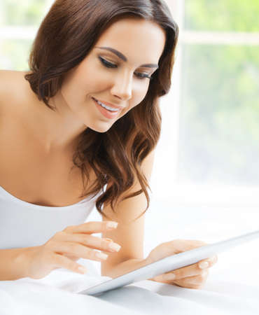 Image of beautiful happy smiling amazed woman using tablet pc, touchpad, looking at, in bed room, near window. Attractive brunette girl at home bedroom.