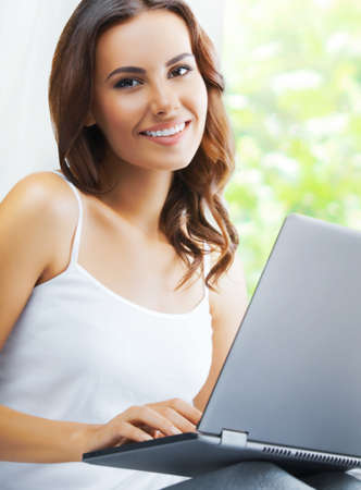 Portrait image of beautiful happy smiling brunette woman using laptop, sitting against window. Working at home, on distance concept.