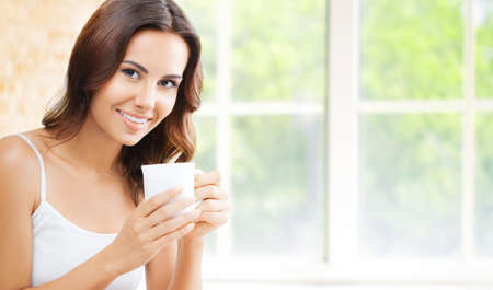 Portrait of happy smiling brunette woman in white lingerie top holding mug cup, drinking coffee or tea, at home, near window and loft style wall.