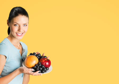 Portrait image of smiling attractive woman in blue casual smart clothing, with plate of fruits, posing at studio over orange yellow color background, with copy space blank area.